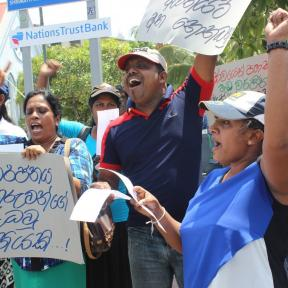 Members of War on Want partner trade union FTZ&GSEU in Sri Lanka, protesting in defence of the right to strike, with fists raised and shouting chants.
