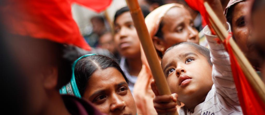 A Bangladeshi boy helps to raise a red flag at a demonstration. He is surrounded by the crowd at the protest, mostly women with headscarves. Credit: Rainbow Collective