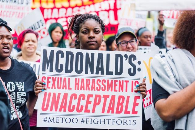 "A Black woman at a demonstration faces the camera holding a sign that reads ""McDonald's: sexual harassment is unacceptable #MeToo #FightFor15. She has black braids with a red streaks, tied up. Credit: FightFor15 Chicago"