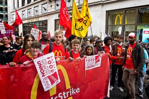 Young striking McDonald's workers take action outside a McDonald's restaurant. They are behind a red McStrike banner that also shows the Bakers Food and Allied Workers Union logo. Credit: Garry Knight