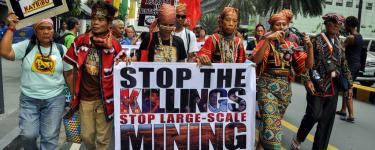 "Kalikasan members march with signs saying ""Mining plunder kills!"" and ""Stop the killings, stop large-scale mining"". Photo: Kalikasan People's Network for the Environment."