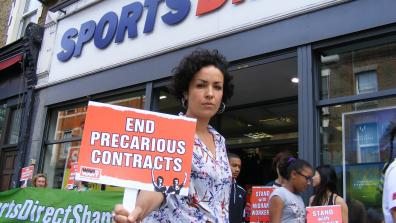 A protestor holds a placard that says 'End Precarious Contracts' outside of a Sports Direct store in Hackney. Credit: War on Want.