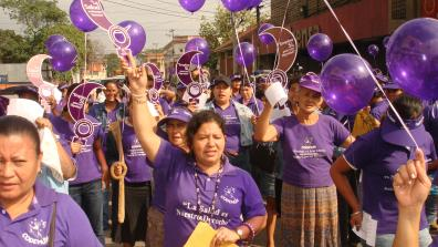 Women workers who are members of Codemuh take part in a street demonstration, wearing purple and holding purple balloons.