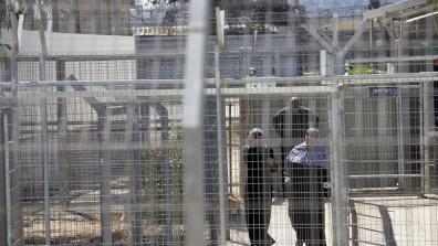 Palestinians walk through the gates of Ofer Military Court and Prison. Photo: Oren Ziv/Activestills
